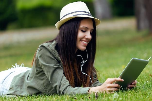 Piękne młoda kobieta przy użyciu cyfrowego tabletu w parku.