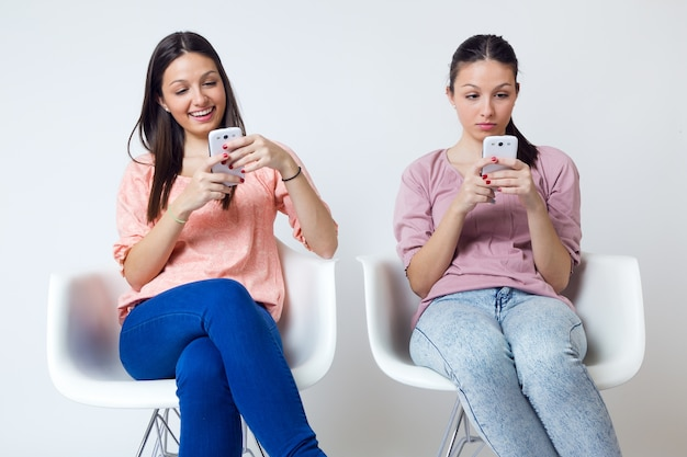 Piękne młoda kobieta przy użyciu swojego telefonu komórkowego w domu.
