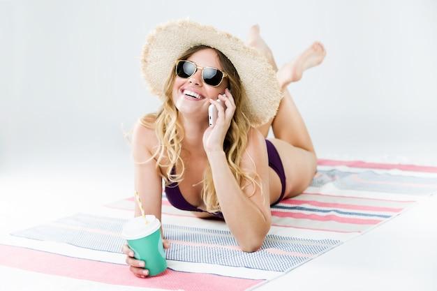 Piękne młoda kobieta w bikini przy użyciu jej telefonu komórkowego. samodzielnie na białym tle.