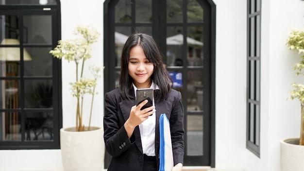 Piękne młode azjatyckie biznes kobieta w garniturze stojącego w kawiarni z telefonem i brązową kopertą