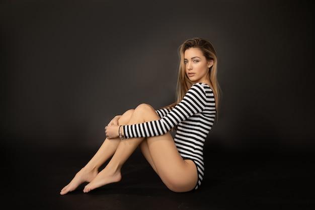 Piękne młode blond długie włosy kobieta ubrana w czarne pasiaste body.