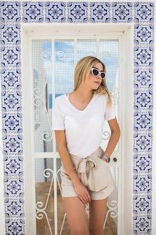 Piękne młode blond kobieta stojąca przy ścianie pokrytej portugalskimi tradycyjnymi kafelkami azulejo.