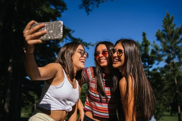 Piękne młode dziewczyny, ciesząc się na zewnątrz i przy selfie.