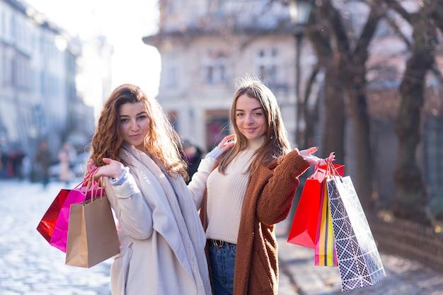Piękne młode dziewczyny robią zakupy w papierowych torebkach i cieszą się i szczęśliwe nowe zakupy
