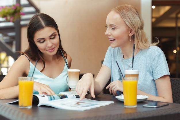 Piękne młode dziewczyny siedzą przy stoliku w kawiarni