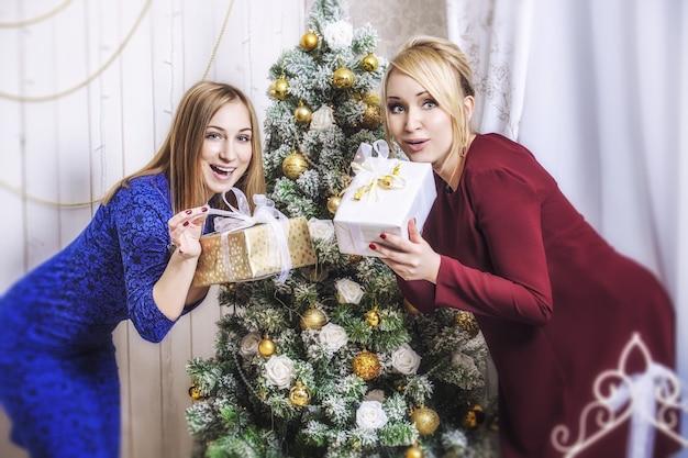 Piękne młode i szczęśliwe dziewczyny wspólnie świętują boże narodzenie