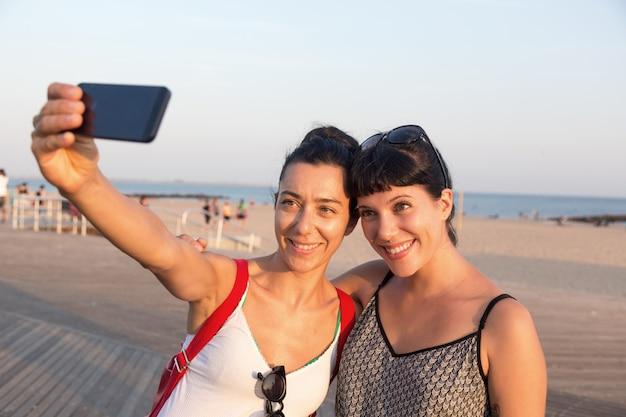 Piękne młode kobiety biorące selfie na coney island