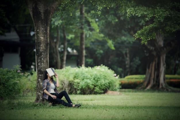 Piękne młode kobiety czyta książkę w parku plenerowym