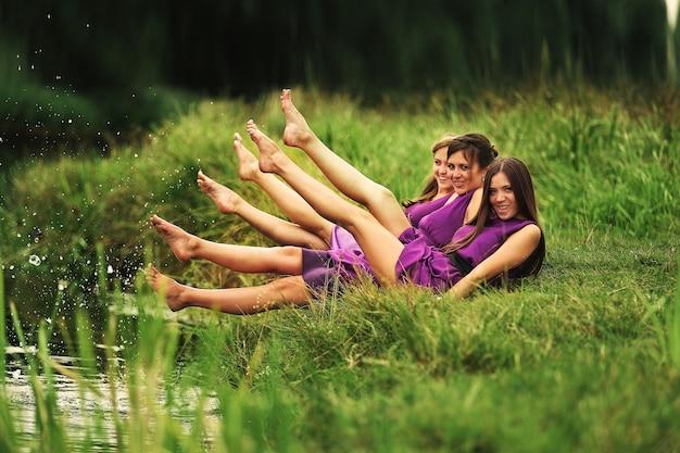 Piękne młode kobiety, druhny w różowych sukienkach bawią się nad jeziorem w ciepły letni dzień. dzień ślubu