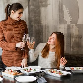 Piękne młode kobiety opiekania kieliszki wina