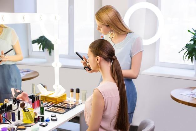 Piękne młode kobiety patrzące w lustro będąc w salonie kosmetycznym