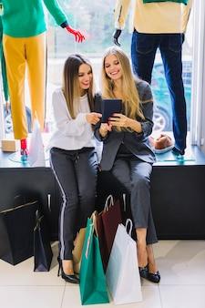 Piękne młode kobiety patrzeje cyfrową pastylkę z kolorowymi torba na zakupy w ubrania przechują