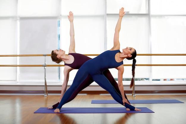 Piękne młode kobiety robią sparowane ćwiczenia rozciągające. dziewczyny na siłowni ćwiczą fitness. pojęcie zdrowia, urody, elastyczności, ruchu życia.