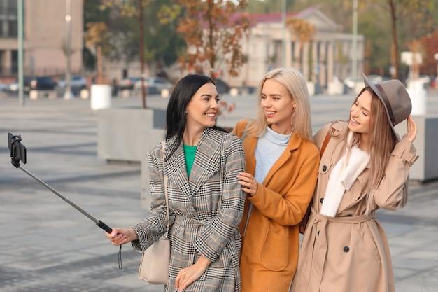 Piękne młode kobiety robiące selfie na zewnątrz