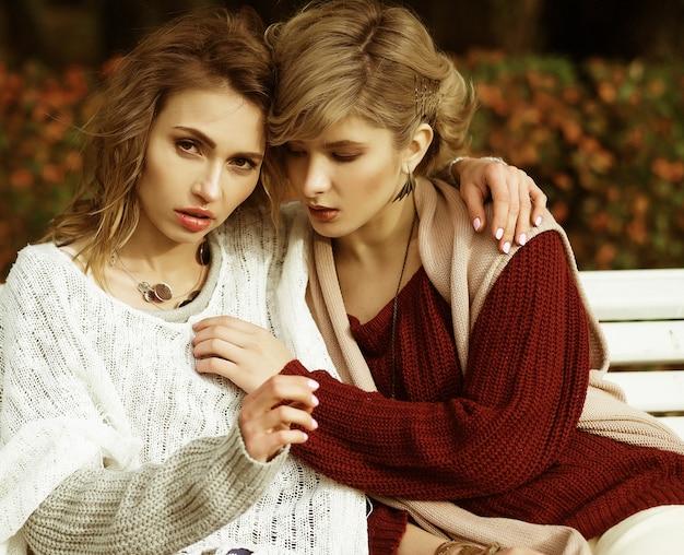 Piękne młode kobiety siedzą na ławce w jesiennym parku