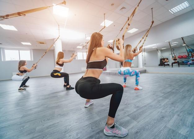 Piękne młode kobiety sportowe ćwiczą z trx na siłowni