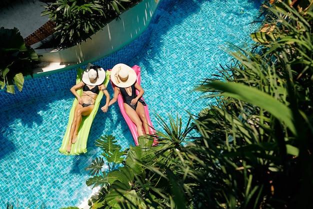 Piękne młode kobiety trzymające się za ręce podczas opalania na pływających materacach w basenie hotelu spa