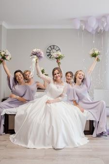 Piękne młode kobiety w jedwabnych koszulach bawiące się w przeddzień ślubu przyjaciela. pogratuluj pannie młodej przyjaźni