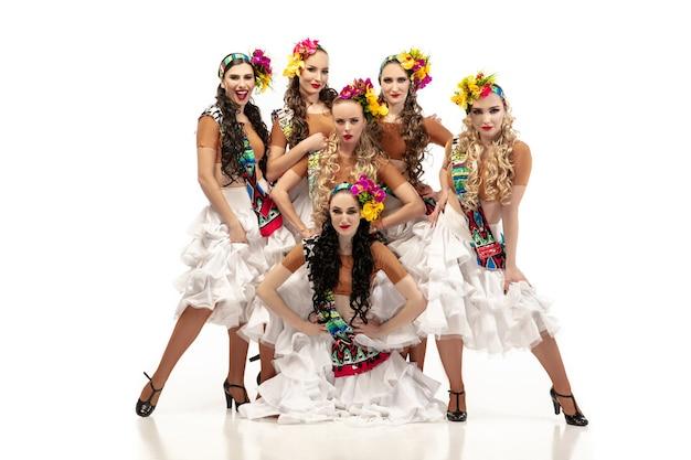 Piękne młode kobiety w karnawałowych i stylowych kostiumach maskarady z kwiatami tańczącymi na białej ścianie studia