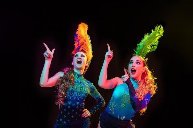 Piękne młode kobiety w karnawałowym, stylowym kostiumie maskaradowym z piórami na czarnej ścianie w neonowym świetle