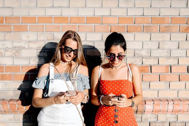 Piękne młode kobiety wysyłają sms-y na telefony komórkowe, stojąc w pobliżu ceglanego muru w słoneczny dzień