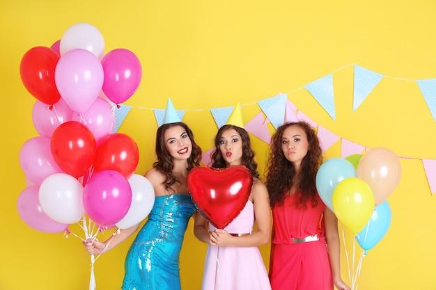 Piękne młode kobiety z balonami powietrznymi na żółtej powierzchni