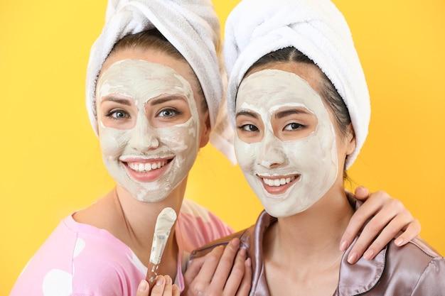 Piękne młode kobiety z maseczkami na twarz na kolorowej powierzchni
