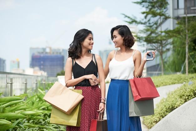 Piękne młode kobiety z papierowymi torbami spacerujące na świeżym powietrzu po wspólnych zakupach w lokalnym centrum handlowym