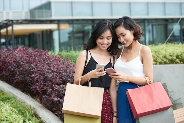 Piękne młode kobiety z torbami na zakupy wysyłające sobie zdjęcia, które zrobiły podczas zakupów w centrum handlowym