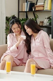 Piękne młode koleżanki w jedwabnej piżamie piją sok pomarańczowy i testują nowy balsam do ciała lub krem do twarzy