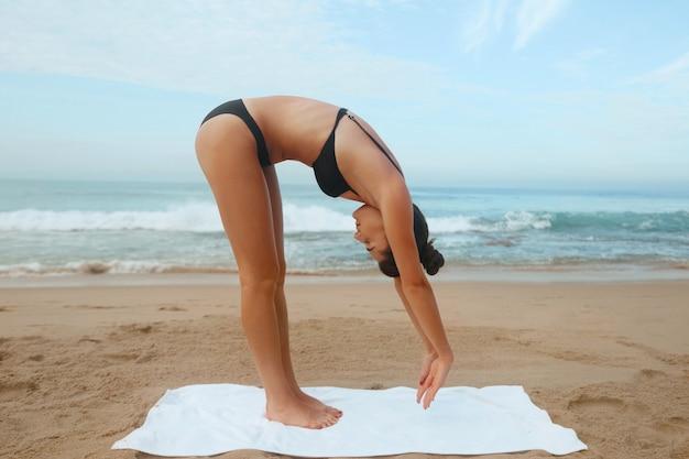 Piękne młode niesamowite ładne fitness kobieta na zewnątrz na plaży zrobić ćwiczenia sportowe jogi. aktywny styl życia. koncepcja zdrowego i jogi.