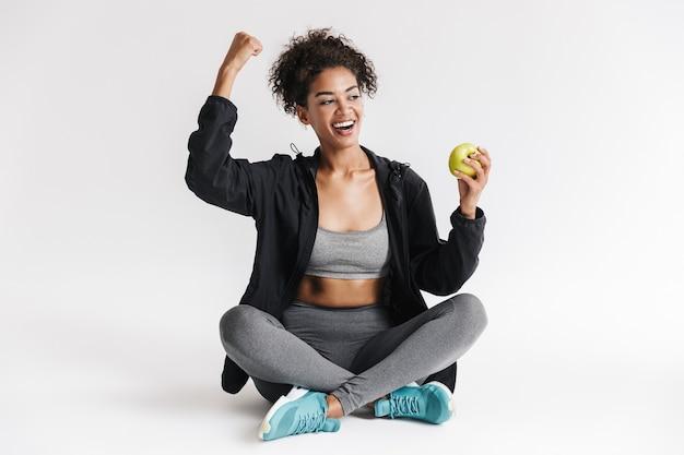 Piękne młode niesamowite sportowe fitness afrykańska kobieta jeść jabłko na białym tle nad białą ścianą.