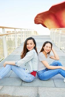 Piękne młode wietnamskie koleżanki siedzące plecami do siebie na moście i uśmiechające się do kamery