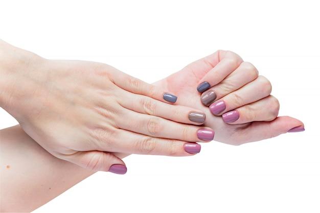 Piękne młodych kobiet ręki odizolowywać na białym tle. stylowy modny kobiecy manicure z szarym, różowym i brązowym lakierem do paznokci.