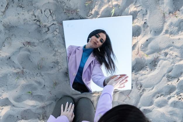Piękne modne młoda kobieta ubrana w czarne body na piasku pozowanie z lustrem. koncepcja mody