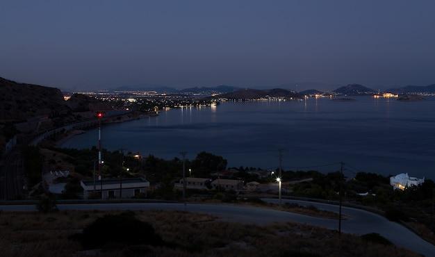 Piękne morze nocnego nieba za lśniącą latarnią morską. grecja