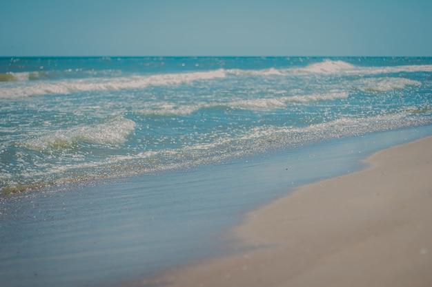 Piękne morze w południe latem z czystą wodą piaszczystą plażą