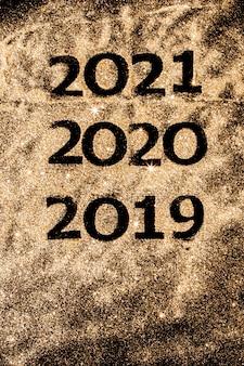 Piękne musujące złote cyfry od 2019 do 2020 na czarnym tle do projektowania