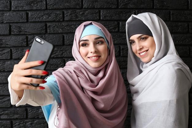 Piękne muzułmanki biorąc selfie na ciemnym tle