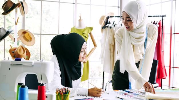 Piękne muzułmańskie kobiety szkicuje odzieżową sylwetkę wpólnie przy biurem.