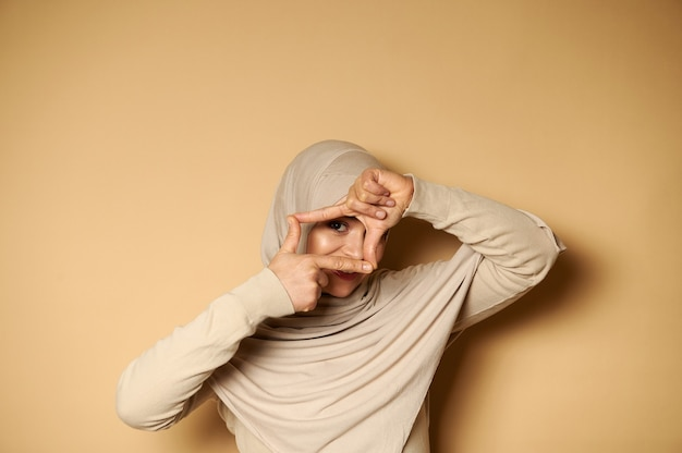 Piękne muzułmańskie kobiety w hidżabie robią ramkę palcami i przeglądają ją