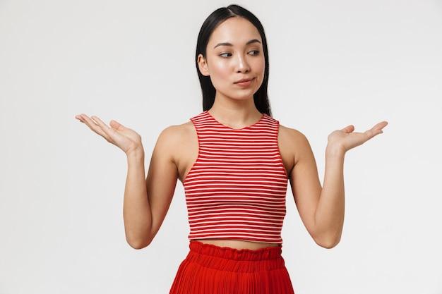 Piękne mylić młode ładne azjatyckie kobiety pozowanie na białym tle nad białą ścianą spróbuj wybrać między dwiema rękami.