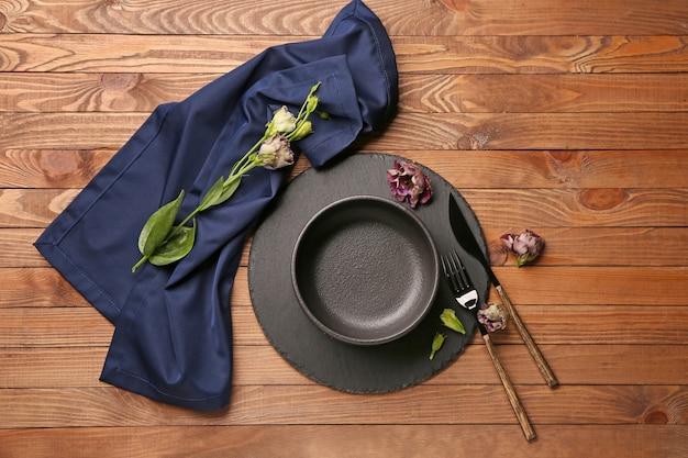Piękne nakrycie stołu z kwiatowym wystrojem na drewnianym