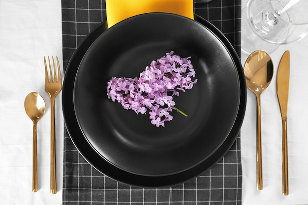 Piękne nakrycie stołu z liliowymi i złotymi sztućcami