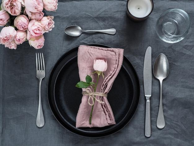 Piękne nakrycie stołu ze świecą na szarym lnianym obrusie. świąteczne nakrycie stołu na kolację weselną z różową różą w sprayu i różową serwetką na talerzu. świąteczny obiad z nowoczesnymi czarnymi talerzami