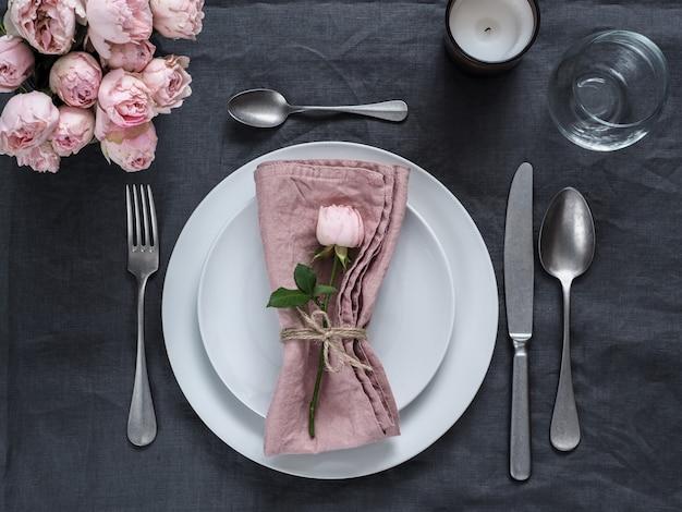 Piękne nakrycie stołu ze świecą na szarym lnianym obrusie.