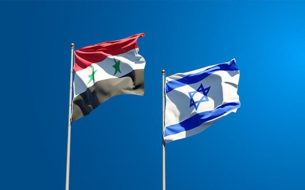 Piękne narodowe flagi państwowe izraela i syrii razem na tle nieba.