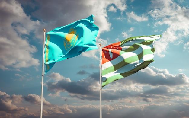 Piękne narodowe flagi państwowe kazachstanu i abchazji razem na błękitnym niebie. grafika 3d
