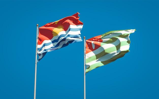 Piękne narodowe flagi państwowe kiribati i abchazji razem na błękitnym niebie. grafika 3d