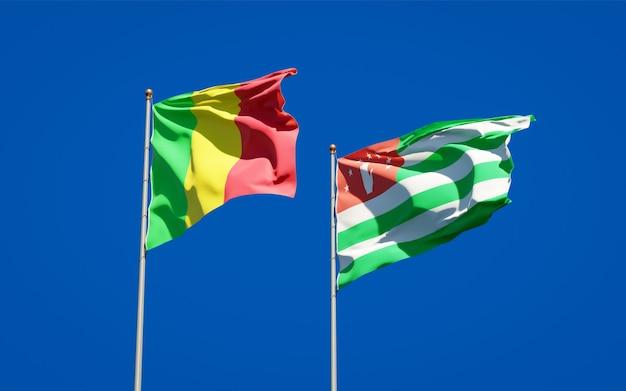Piękne narodowe flagi państwowe mali i abchazji razem na błękitnym niebie. grafika 3d